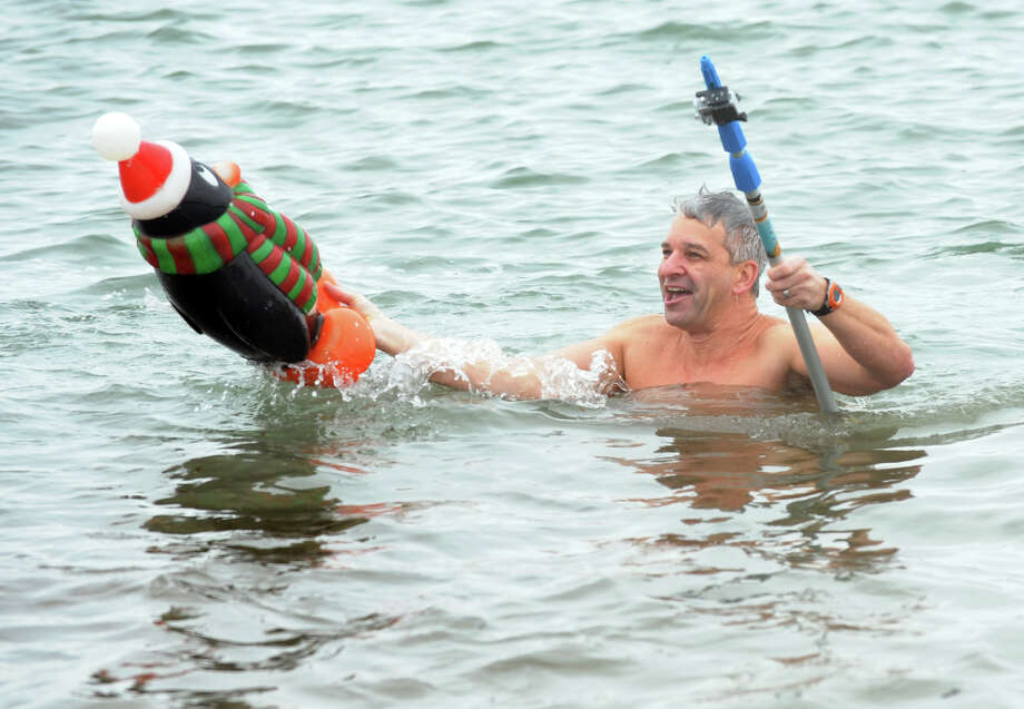 "Ken Osborn of Prospect, carries ""Pete"" the penguin as he takes part in a polar plunge which was held to benefit two charities named for two victims of the Newtown tragedy, at Southport Beach in Southport, Conn. on Saturday January 12, 2013. Money raised goes to the Grace McDonnell Memorial Fund and the Glenn Atkinson Memorial Scholarship Fund. Photo: Christian Abraham / Connecticut Post"