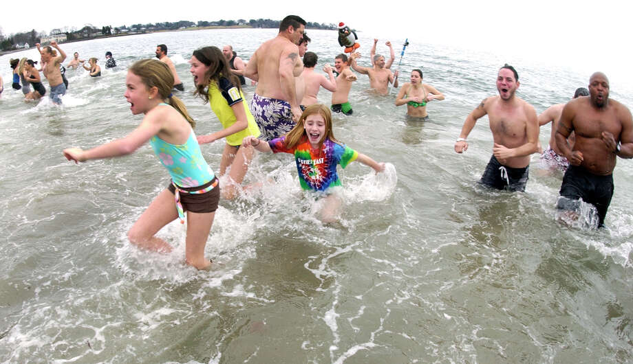 Shocked kids and adults alike rush back to shore as they take part in a polar plunge which was held to benefit two charities named for two victims of the Newtown tragedy, at Southport Beach in Southport, Conn. on Saturday January 12, 2013. Money raised goes to the Grace McDonnell Memorial Fund and the Glenn Atkinson Memorial Scholarship Fund. Photo: Christian Abraham / Connecticut Post