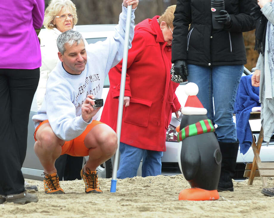 "Ken Osborn of Prospect, takes a picture of the unofficial event mascott, ""Pete"" the penguin, as he takes part in a polar plunge which was held to benefit two charities named for two victims of the Newtown tragedy, at Southport Beach in Southport, Conn. on Saturday January 12, 2013. Money raised goes to the Grace McDonnell Memorial Fund and the Glenn Atkinson Memorial Scholarship Fund. Photo: Christian Abraham / Connecticut Post"
