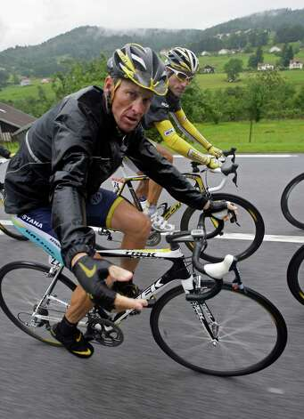 American seven-time Tour de France winner Lance Armstrong, foreground, gestures as he rides with fellow countryman George Hincapie, rear, during the 13th stage of the Tour de France cycling race over 200 kilometers (124.3 miles) with start in Vittel and finish in Colmar, central France, Friday July 17, 2009. (AP Photo/Bas Czerwinski) Photo: BAS CZERWINSKI, Associated Press / AP