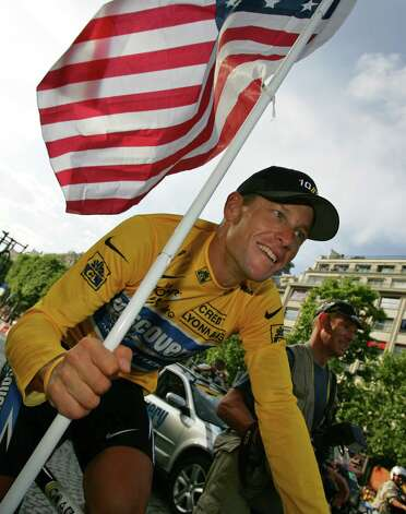 Lance Armstrong, of Austin, Texas, carries the Stars and Stripes during a victory parade on the Champs Elysees after winning his seventh straight Tour de France cycling race in Paris, the French capital July 24, 2005.  (AP Photo/Peter Dejong) Photo: PETER DEJONG, Associated Press / AP