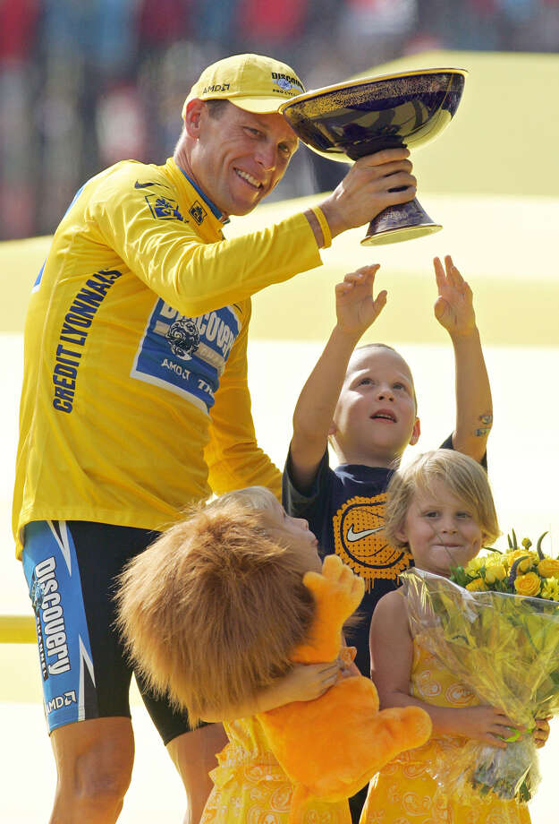 Luke Armstrong, rear right, tries to touch the winner's trophy held by his father Lance Armstrong, of Austin, Texas, after Armstrong won his seventh straight Tour de France cycling race, during ceremonies on the Champs-Elysees avenue in Paris, after the 21st and final stage of the race between Corbeil-Essonnes, south of Paris, and the French capital, Sunday, July 24, 2005. Armstrong's twin daughters Grace, right, and Isabelle, look on. (AP Photo/Peter Dejong) Photo: PETER DEJONG, Associated Press / AP