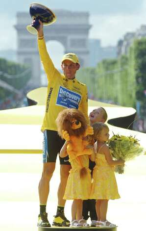 Lance Armstrong, of Austin, Texas, holds the winner's trophy as his son Luke, rear right, his twin daughters Grace, right, and Isabelle, look on, after winning his seventh straight Tour de France cycling race, during ceremonies on the Champs-Elysees avenue in Paris, after the 21st and final stage of the race between Corbeil-Essonnes, south of Paris, and the French capital, in July 24, 2005. The Arc de Triomphe is seen behind. (AP Photo/Bernard Papon) Photo: BERNARD PAPON, Associated Press / POOL L'EQUIPE