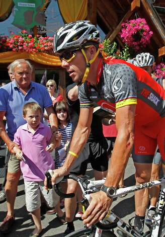 A child looks at seven-time Tour de France winner Lance Armstrong of the US as he leaves for a training ride on the rest day of the Tour de France cycling race in Morzine-Avoriaz, France, Monday, July 12, 2010.  (AP Photo/Bas Czerwinski) Photo: Bas Czerwinski, Associated Press / AP