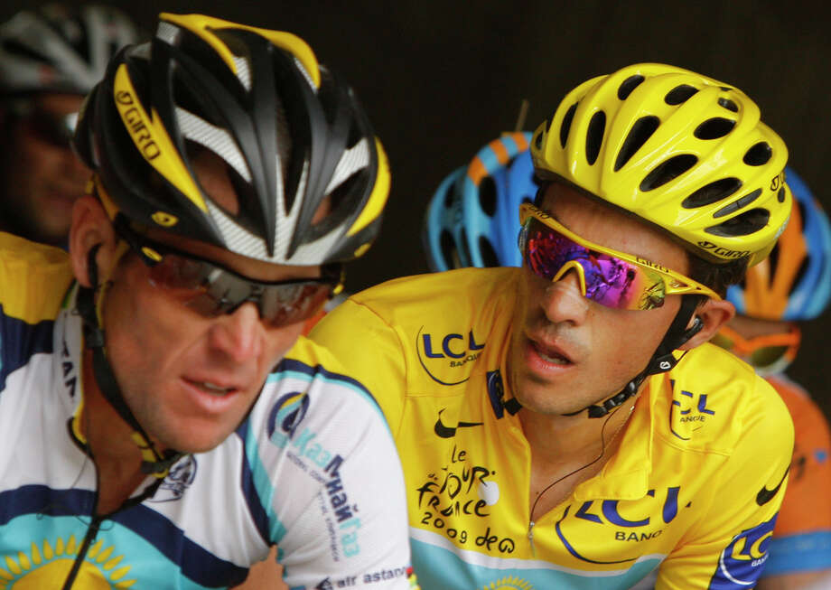Alberto Contador, right, of Spain, wearing the overall leader's yellow jersey, looks at American seven-time Tour de France winner Lance Armstrong, as they climb Grand-Saint-Bernard pass July 21, 2009 during the 16th stage of the Tour de France cycling race over 159 kilometers (98.8 miles) which started in Martigny, Switzerland and finished in Bourg-Saint-Maurice, France.   (AP Photo/Christophe Ena) Photo: CHRISTOPHE ENA, Associated Press / AP2009