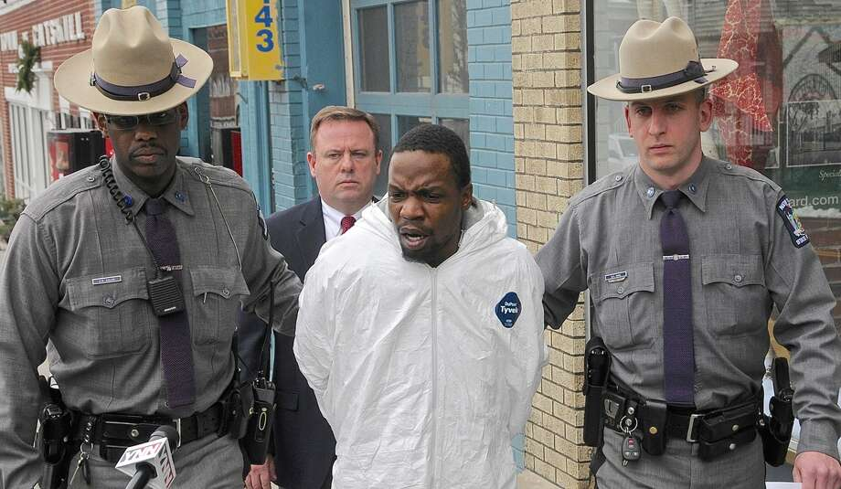 Maurice Pratt (center in white jumpsuit) is led by State Troopers Amauris Soler (left) , Senior Investigator Scott Youngblood , Maurice Pratt, and Trooper Bernard Davis