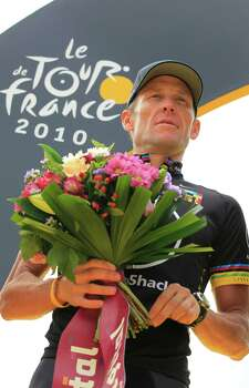 Lance Armstrong of the US holds flowers during the podium ceremony for the best team after the 20th and last stage of the Tour de France cycling race over 102.5 kilometers (63.7 miles) with start in Longjumeau and finish in Paris, France, Sunday, July 25, 2010. (AP Photo/Bas Czerwinski) Photo: Bas Czerwinski, Associated Press / AP