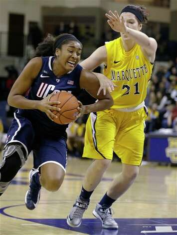 UConn's Morgan Tuck, left, drives against Marquette's Katherine Plouffe (21) during the second half of an NCAA college basketball game Saturday, Jan. 12, 2013, in Milwaukee. (AP Photo/Jeffrey Phelps)