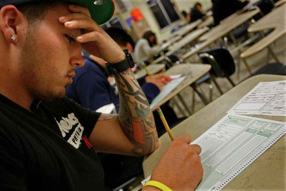 Luis Luna takes a placement exam in Los Angeles in an effort to earn his high school diploma. He was deported before he could graduate from high school. Photo: Don Bartletti, MBR / Los Angeles Times