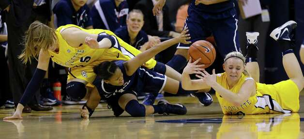 Connecticut's Moriah Jefferson, middle, reaches for a loose ball against Marquette's Cristina Bigica, left, and Brooklyn Pumroy, right, in the first half of an NCAA college basketball game Saturday, Jan. 12, 2013, in Milwaukee. (AP Photo/Jeffrey Phelps) Photo: Jeffrey Phelps, Associated Press / FR59249 AP