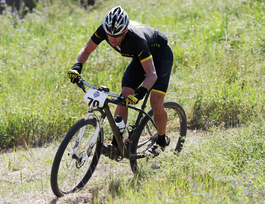 Lance Armstrong negotiates the route on his way to a second-place finish in the Power of Four mountain bicycle race at the base of Aspen Mountain in Aspen, Colo., on Saturday, Aug. 25, 2012. The race is the first public appearance for Armstrong since the U.S. Anti-Doping Association stripped him of his seven Tour de France championships and banned him for life from professional cycling. (AP Photo/David Zalubowski) Photo: David Zalubowski, Associated Press / AP