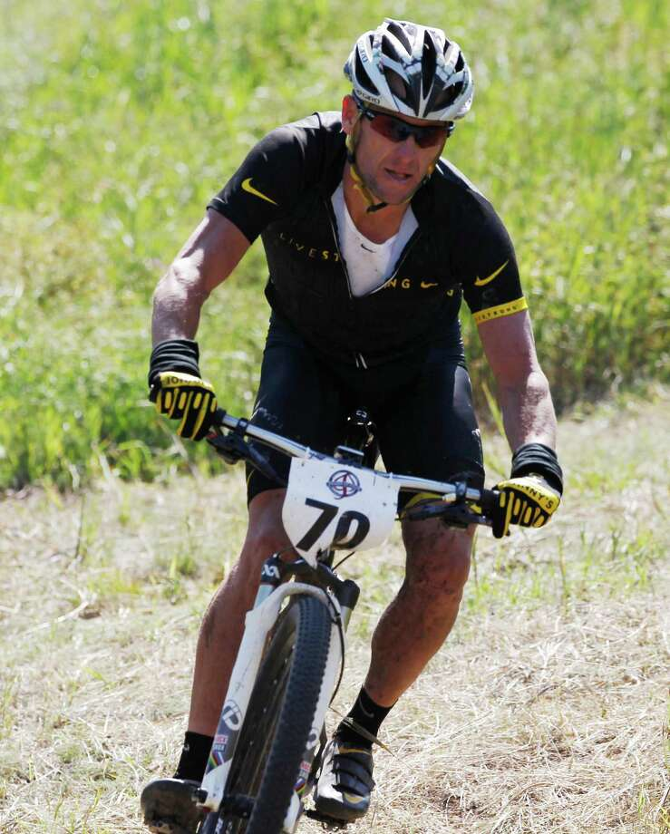 Lance Armstrong negotiates the final turn on the way to his second-place finish in the Power of Four mountain bicycle race at the base of Aspen Mountain in Aspen, Colo., on Saturday, Aug. 25, 2012. The race is the first public appearance for Armstrong since the U.S. Anti-Doping Association stripped him of his seven Tour de France championships and banned him for life from professional cycling. (AP Photo/David Zalubowski) Photo: David Zalubowski, Associated Press / AP