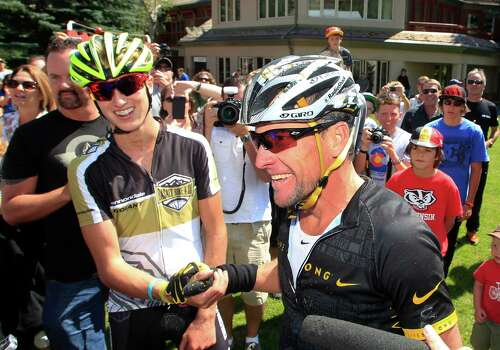 Lance Armstrong, front, talks to reporters after his second-place finish in the Power of Four mountain bicycle race at the base of Aspen Mountain in Aspen, Colo., on Saturday, Aug. 25, 2012. Race-winner Keegan Swirbul, 16, of Aspen, left, clapso his hand. The race is the first public appearance for Armstrong since the U.S. Anti-Doping Association stripped him of his seven Tour de France championships and banned him for life from professional cycling. (AP Photo/David Zalubowski) Photo: David Zalubowski, Associated Press / AP