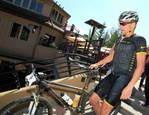 Lance Armstrong guides his bicycle down the steps after his second-place finish in the Power of Four mountain bicycle race at the base of Aspen Mountain in Aspen, Colo., on Saturday, Aug. 25, 2012. The race is the first public appearance for Armstrong since the U.S. Anti-Doping Association stripped him of his seven Tour de France championships and banned him for life from professional cycling. (AP Photo/David Zalubowski) Photo: David Zalubowski, Associated Press / AP