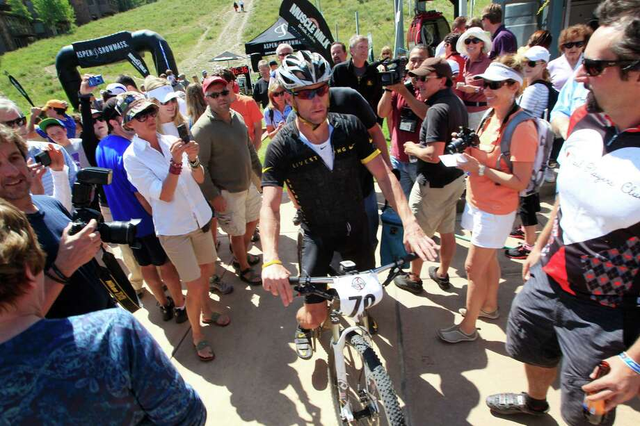 Lance Armstrong guides his bicycle through the small crowd after his second-place finish in the Power of Four mountain bicycle race at the base of Aspen Mountain in Aspen, Colo., on Saturday, Aug. 25, 2012. The race is the first public appearance for Armstrong since the U.S. Anti-Doping Association stripped him of his seven Tour de France championships and banned him for life from professional cycling. (AP Photo/David Zalubowski) Photo: David Zalubowski, Associated Press / AP