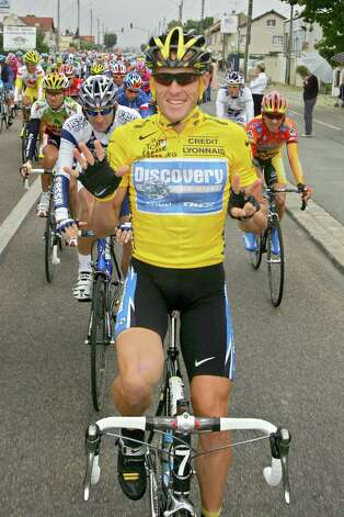 Overall leader Lance Armstrong, of Austin, Texas, signals seven for his seventh straight win in the Tour de France cycling race July 24, 2005, as he pedals during the 21st and final stage of the race between Corbeil-Essonnes, south of Paris, and the French capital.  (AP Photo/Peter Dejong) Photo: PETER DEJONG, Associated Press / AP2005