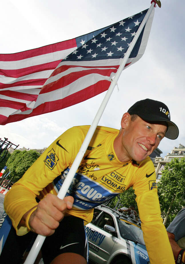 Lance Armstrong, of Austin, Texas, carries the United States flag during a victory parade on the Champs Elysees avenue in Paris, July 24, 2005, after winning his seventh straight Tour de France cycling race.  (AP Photo/Peter Dejong) Photo: PETER DEJONG, Associated Press / AP