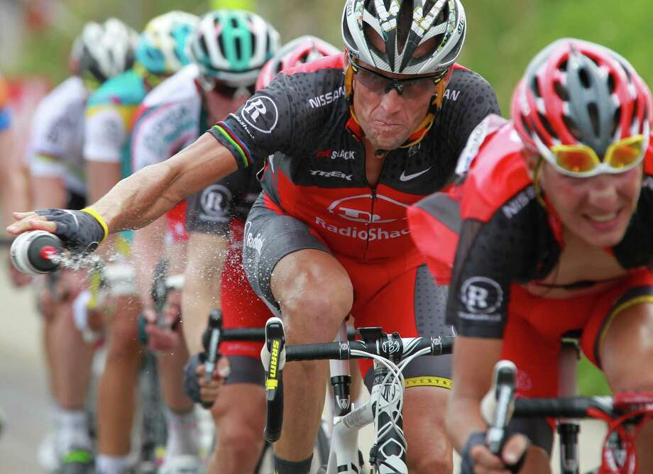 Lance Armstrong throws out his water bottle in the last kilometers of the climb toward Station les Rousses, France, July 10, 2010, during the seventh stage of the Tour de France cycling race. The New York Times reported Friday, Jan. 4, 2013, that Armstrong, who has strongly denied the doping charges that led to him being stripped of his seven Tour de France titles, has told associates he is considering admitting to the use of performance-enhancing drugs.  (AP Photo/Bas Czerwinski) Photo: Bas Czerwinski, Associated Press / AP
