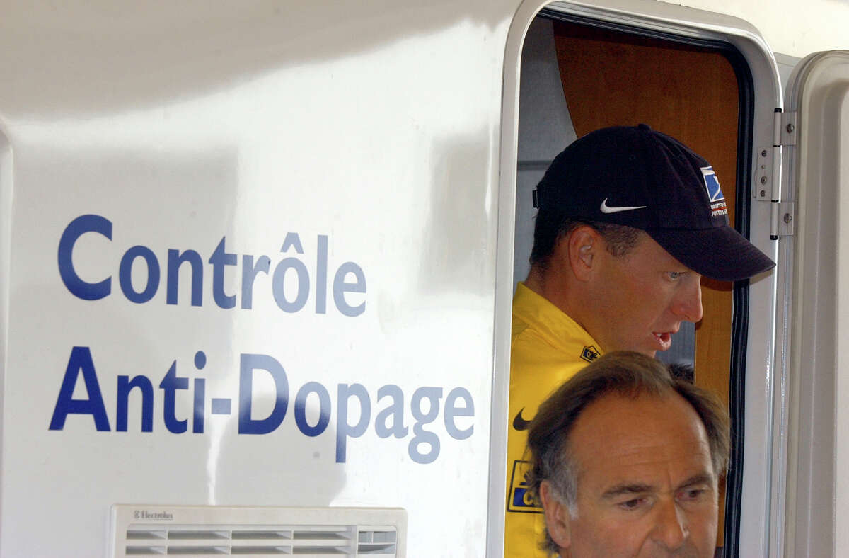 Lance Armstrong walks out of the Tour de France's anti-doping control bus July 24, 2002 after the 16th stage of the Tour de France cycling race between Les Deux Alpes and La Plagne, French Alps. (AP Photo/Peter Dejong)