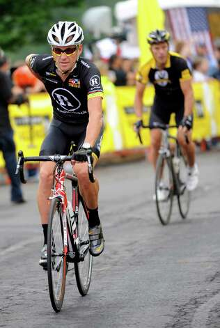 FILE- In this Aug. 22, 2010 file photo, cyclist Lance Armstrong, left, pedals off at the start of his Livestrong Challenge 10K ride for cancer in Blue Bell, Pa.  Even after whistleblowers unveiled their scathing report portraying Armstrong as an unrepentant drug cheat, the argument over what to make of his life story rages on.  (AP Photo/Bradley C. Bower, File) Photo: Bradley C Bower, Associated Press / FR37962 AP