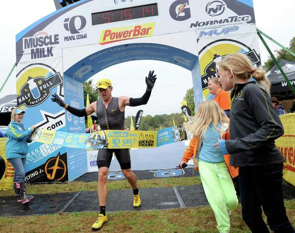 Lance Armstrong crosses the finish line of the Rev3 Half Full Triathalon Sunday, Oct. 7, 2012 in Ellicott City, Md. Armstrong joined other cancer survivors in the event which raised funds for the Ulman Cancer Fund for Young Adults. (AP Photo/Steve Ruark) Photo: Steve Ruark, Associated Press / FR96543 AP