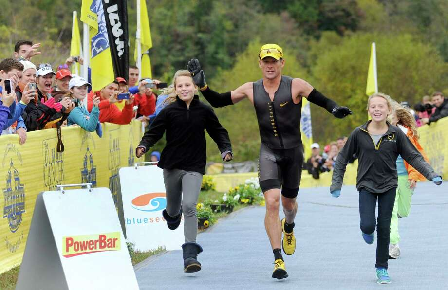 Lance Armstrong crosses the finish line of the Rev3 Half Full Triathalon with his ten-year-old twin daughters Grace, left, and Isabelle, right, Sunday, Oct. 7, 2012 in Ellicott City, Md. Armstrong joined other cancer survivors in the event which raised funds for the Ulman Cancer Fund for Young Adults. (AP Photo/Steve Ruark) Photo: Steve Ruark, Associated Press / FR96543 AP