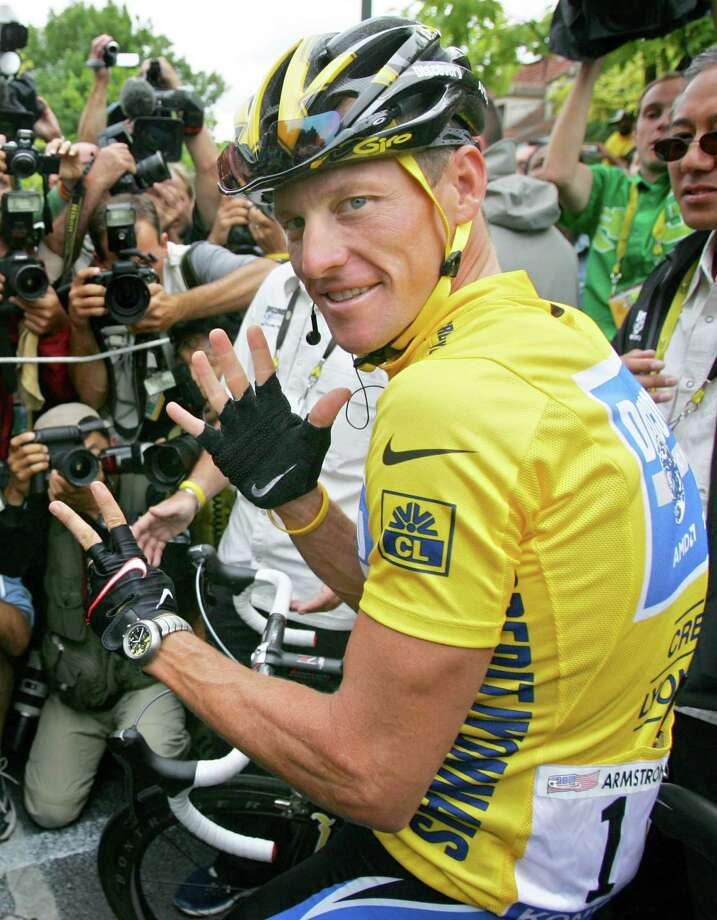 Overall leader Lance Armstrong, of Austin, Texas, surrounded by press photographers July 24, 2005, signals seven,  for his seventh straight win in the Tour de France cycling race, prior to the start of the 21st and final stage of the race,  between Corbeil-Essonnes, south of Paris, and the French capital.   (AP Photo/Peter Dejong) Photo: PETER DEJONG, Associated Press / AP