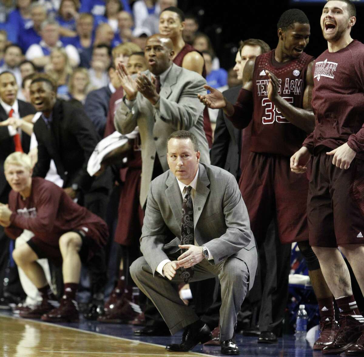 Texas A&M head coach Billy Kennedy, bottom center, watches the closing moments while the bench celebrates behind him late in the second half of an NCAA college basketball game against Kentucky at Rupp Arena in Lexington, Ky., Saturday, Jan. 12, 2013. Texas A&M won 83-71. (AP Photo/James Crisp)