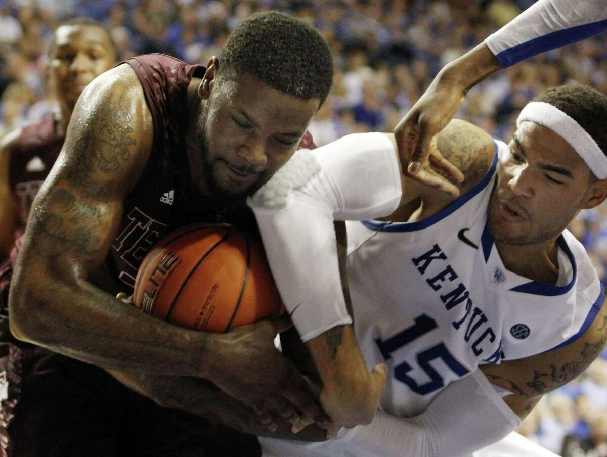 Texas A&M's Kourtney Roberson, left, is pressured by Kentucky's Willie Cauley-Stein during the second half of an NCAA college basketball game at Rupp Arena in Lexington, Ky., Saturday, Jan. 12, 2013. Texas A&M defeated Kentucky 83-71. (AP Photo/James Crisp)