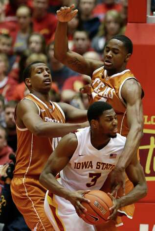 Iowa State forward Melvin Ejim, center, drives between Texas defenders Texas Jonathan Holmes, left, and Prince Ibeh, right, during the second half of an NCAA college basketball game, Saturday, Jan. 12, 2013, in Ames, Iowa. Iowa State won 82-62. (AP Photo/Charlie Neibergall) Photo: Charlie Neibergall, Associated Press / AP