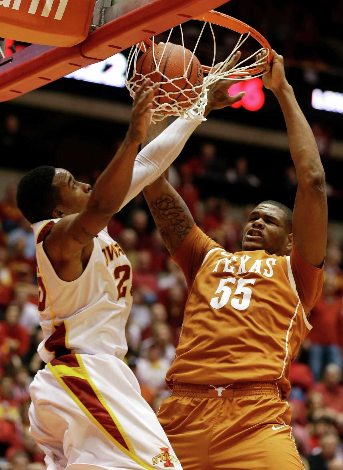 Texas center Cameron Ridley (55) dunks the ball over Iowa State guard Tyrus McGee, left, during the second half of an NCAA college basketball game, Saturday, Jan. 12, 2013, in Ames, Iowa. Iowa State won 82-62. (AP Photo/Charlie Neibergall)