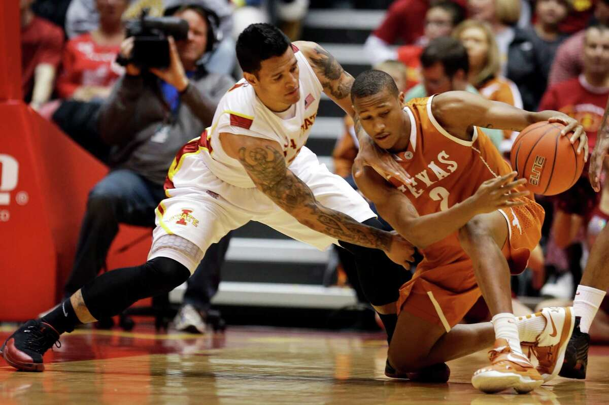 Iowa State guard Chris Babb, left, tries to steal the ball from Texas guard Demarcus Holland during the first half of an NCAA college basketball game, Saturday, Jan. 12, 2013, in Ames, Iowa. (AP Photo/Charlie Neibergall)