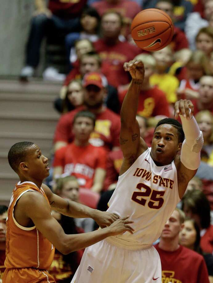 Iowa State guard Tyrus McGee, right, passes the ball over Texas guard Demarcus Holland during the second half of an NCAA college basketball game on Saturday, Jan. 12, 2013, in Ames, Iowa. Iowa State won 82-62. (AP Photo/Charlie Neibergall) Photo: Charlie Neibergall, Associated Press / AP