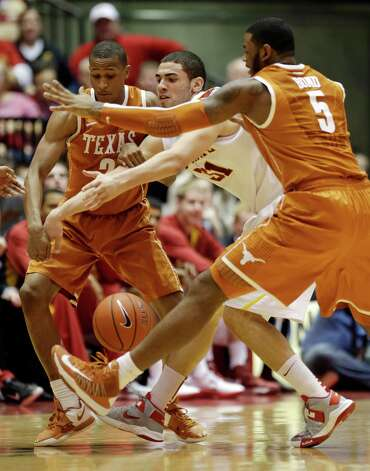 Iowa State forward Georges Niang, center, fights for a loose ball with Texas' Demarcus Holland, left, and Jaylen Bond, right, during the second half of an NCAA college basketball game, Saturday, Jan. 12, 2013, in Ames, Iowa. Niang scored 18 points in Iowa State's 82-62 win. (AP Photo/Charlie Neibergall) Photo: Charlie Neibergall, Associated Press / AP