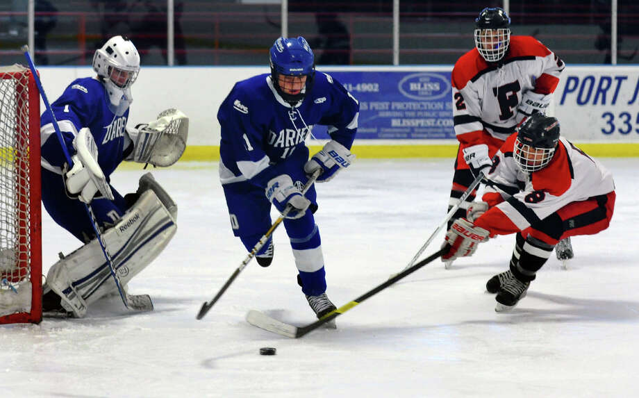 Darien's #11 Nicholas Tuzinkiewicz center, disrupts a drive to the goal by Fairfield Warde/Ludlowe's #8 Michael Aquila, during boys hockey action at the Wonderland of Ice in Bridgeport, Conn. on Saturday January 12, 2013. Defending the goal is Darien's Michael Colon. Photo: Christian Abraham / Connecticut Post