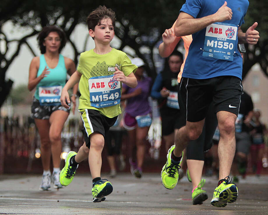 Seven-year-old Sam Saman, center, nears the finish line of the ABB 5K race during the Houston Marathon race weekend Saturday, Jan. 12, 2013, in Houston. Photo: James Nielsen, Chronicle / © Houston Chronicle 2013