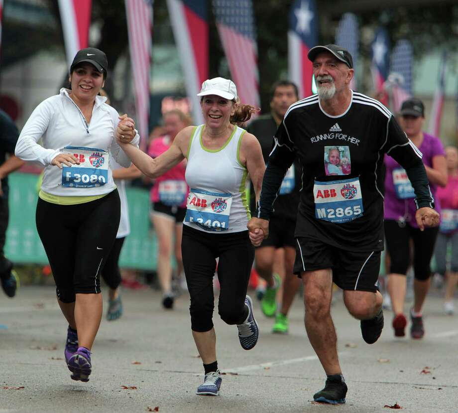 Carolina Cutrera, left, Monica Cutrera, center, and Roberton Cutrera, right, run hand in hand as they near the finish line of the ABB 5K race during the Houston Marathon race weekend Saturday, Jan. 12, 2013, in Houston. Photo: James Nielsen, Chronicle / © Houston Chronicle 2013