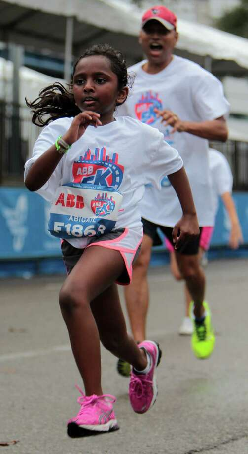 Daniel Samuel, left, cheers on nine-year-old Abigail Samuel right, as the pair near the finish line of the ABB 5K race during the Houston Marathon race weekend Saturday, Jan. 12, 2013, in Houston. Photo: James Nielsen, Chronicle / © Houston Chronicle 2013