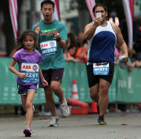 Seven-year-old Megan Phan, left, nears the finish line as Dung Quach, center, cheers and Dan Ly takes a photograph while running in the ABB 5K race during the Houston Marathon race weekend Saturday, Jan. 12, 2013, in Houston. Photo: James Nielsen, Chronicle / © Houston Chronicle 2013