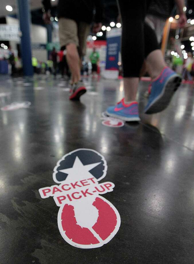 Decals on the floor mark the path to the packet pick-up location at the Chevron Houston Marathon Expo at the George R. Brown Convention Center Saturday, Jan. 12, 2013, in Houston. Photo: James Nielsen, Chronicle / © Houston Chronicle 2013