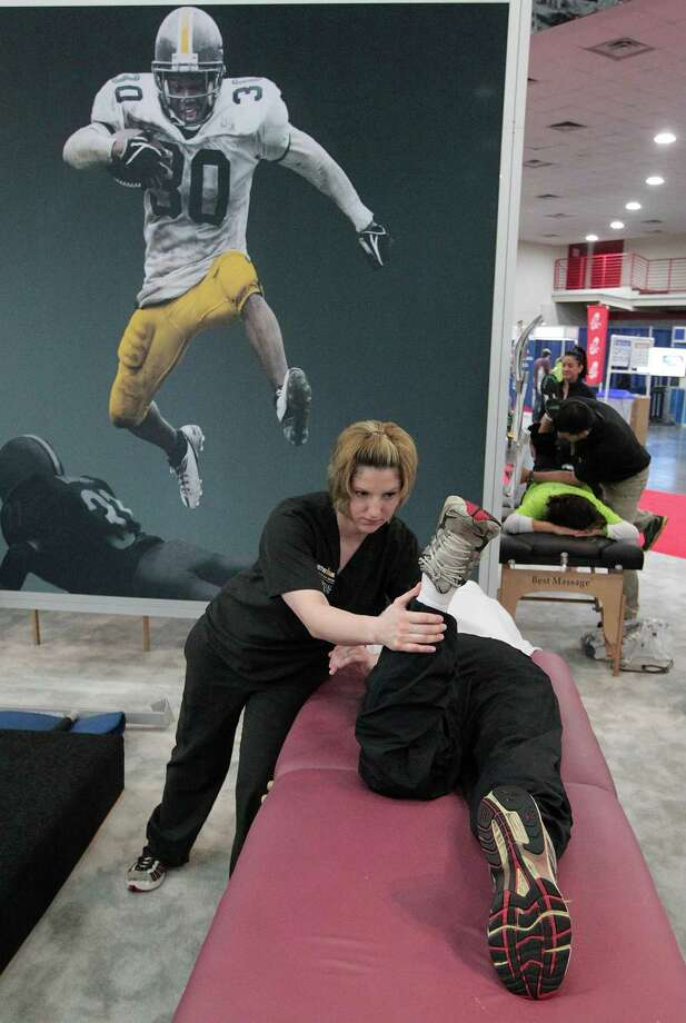 Rebekah Palaian with the Ironman Sports Medicine Institute at Memorial Hermann gives Crawford Gallien a massage as he prepares to run his third half-marathon on Sunday, during the Chevron Houston Marathon Expo at the George R. Brown Convention Center Saturday, Jan. 12, 2013, in Houston. Photo: James Nielsen, Chronicle / © Houston Chronicle 2013