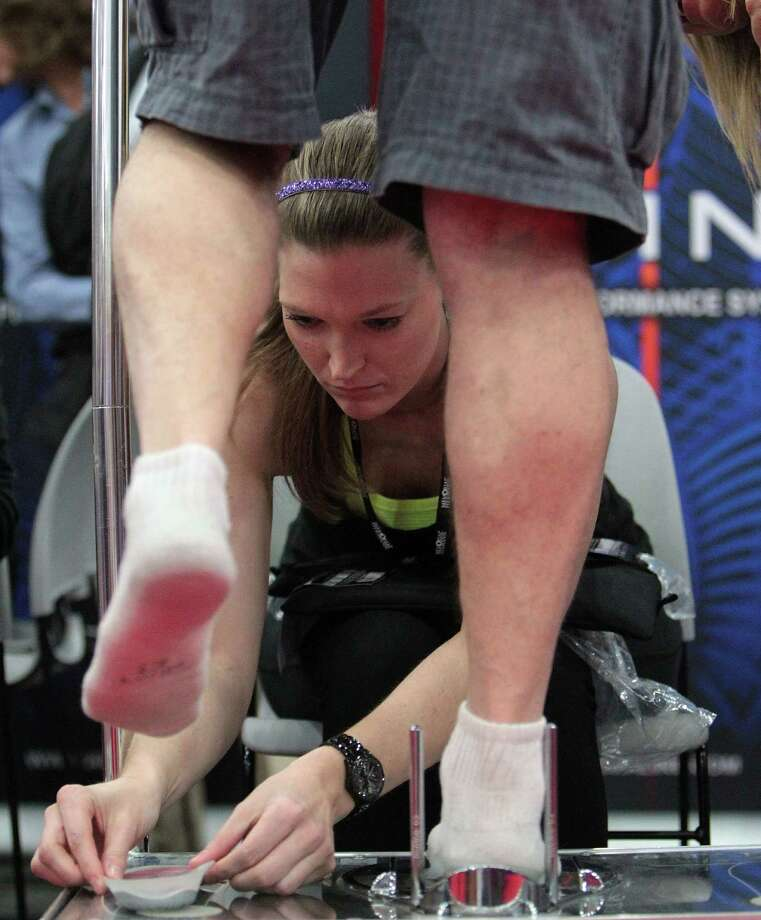 Miranda Schmutz fits a runner with an Aline suspension system insole during the Chevron Houston Marathon Expo at the George R. Brown Convention Center Saturday, Jan. 12, 2013, in Houston. Photo: James Nielsen, Chronicle / © Houston Chronicle 2013