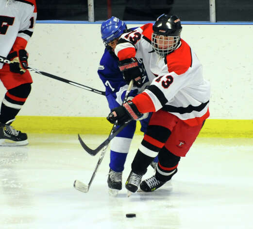 Fairfield Warde/Ludlowe's #13 Charlie Meder gets in front of Darien's #7 Jack Knowlton to moves the puck, during boys hockey action at the Wonderland of Ice in Bridgeport, Conn. on Saturday January 12, 2013. Photo: Christian Abraham / Connecticut Post