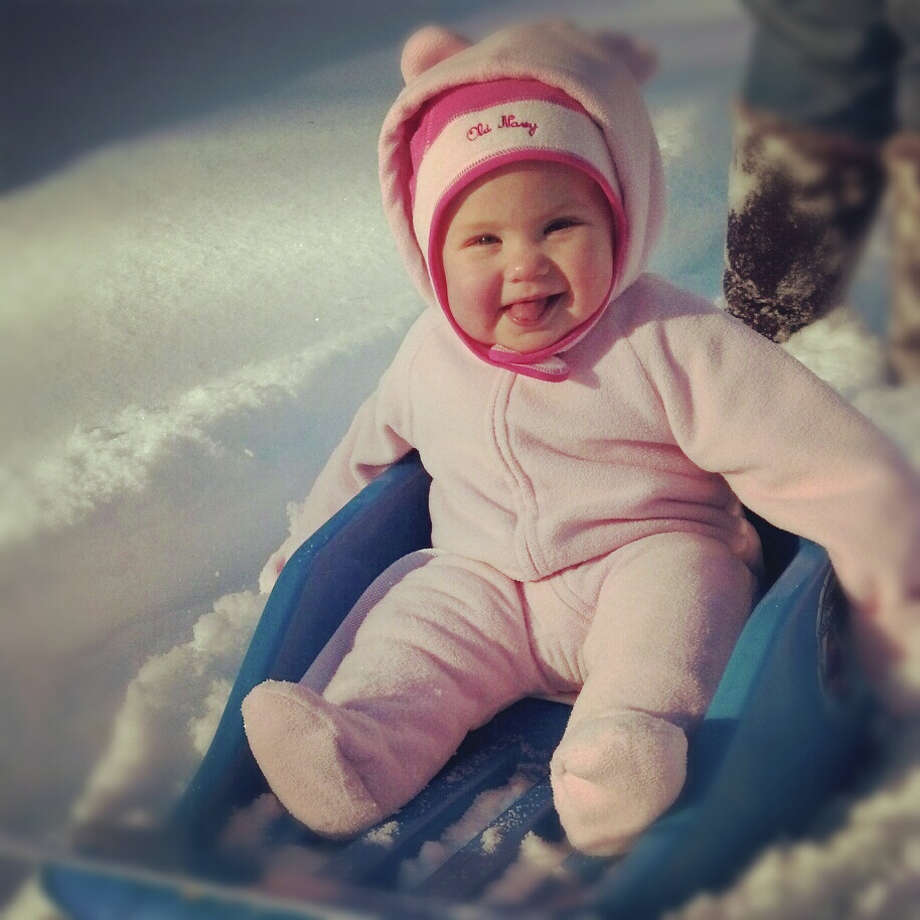 Six-month-old Zoey McConnelee, the daughter of Lorijo and Chad McConnelee of Schenectady, enjoys her first time in the snow and her first time sledding in the Adirondack Mountain town of Paradox on Dec. 30. (Kelley Waleski)