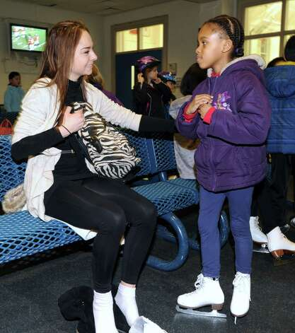 At right, Coreen Valbrun, 7, of Greenwich, speaks with Elena Glebova, an Estonian national figure skating champion, during a visit by Glebova to the Boys & Girls Club of Greenwich, Saturday night, Jan. 12, 2013. Photo: Bob Luckey / Greenwich Time