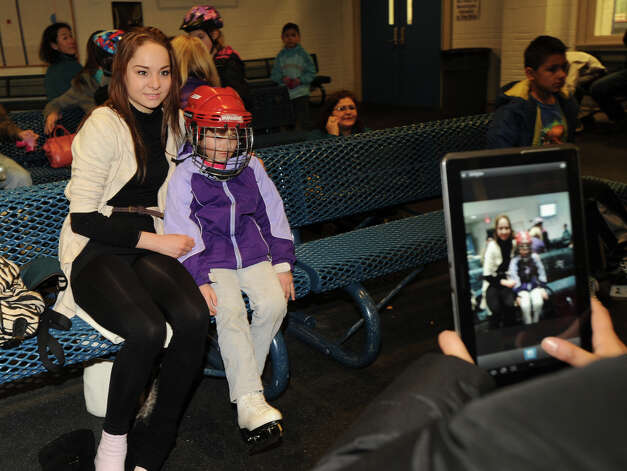 At right, Tabitha Bodian, 6, of Greenwich, gets her photo taken with Elena Glebova, an Estonian national figure skating champion, during a visit by Glebova to the Boys & Girls Club of Greenwich, Saturday night, Jan. 12, 2013. Photo: Bob Luckey / Greenwich Time