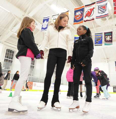 Greenwich residents, Hayley Judice, left, 9, and Sherlynn Arcuri, right, also 9, speak with Elena Glebova, an Estonian national figure skating champion, during a visit by Glebova to the Boys & Girls Club of Greenwich, Saturday night, Jan. 12, 2013. Photo: Bob Luckey / Greenwich Time
