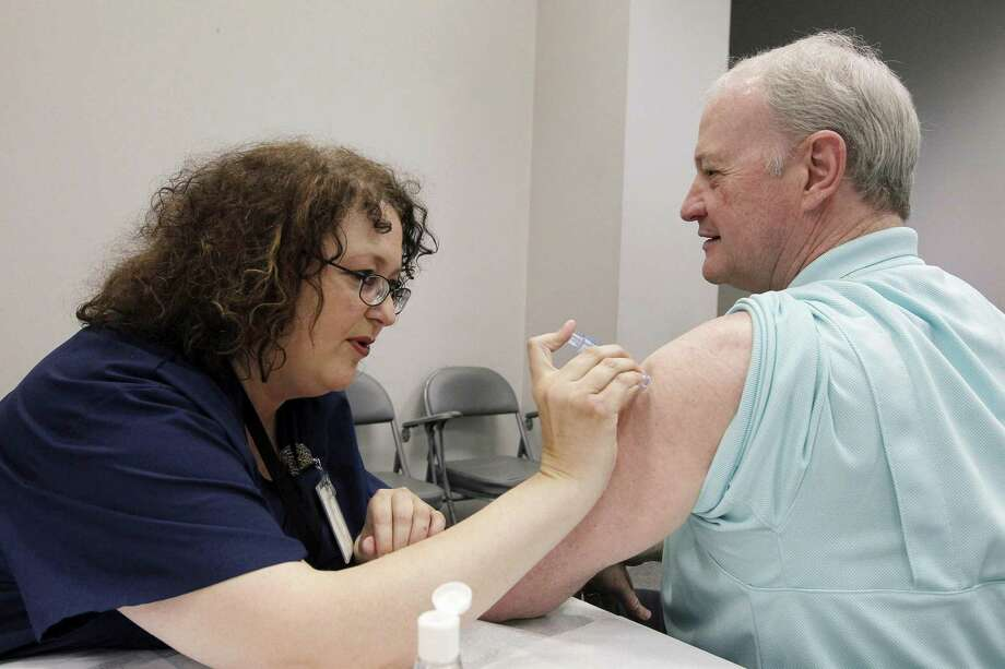 Most health care workers, like this Mississippi Department of Health employee in a photo taken in October, do get flu shots. Those who refuse can be fired. Photo: Rogelio V. Solis, STF / AP