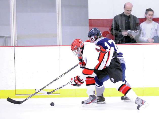 At left, Mike Stroumbakis # 11 of Greenwich, fights for control of the puck against Sean Stewart # 17 of SWS during the boys high school ice hockey game between Staples-Weston-Shelton High School and Greenwich High School at Hamill Rink in Byram, Saturday night, Jan. 12, 2013. Photo: Bob Luckey / Greenwich Time