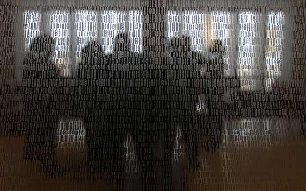 Guests are seen through a glass partition featuring unique patterns at the unveiling ceremony of the new Clinical Pavilion at the Robert B. Green Campus of the University Health System was held on Saturday, Jan. 12, 2013. The outpatient clinic features urgent and primary care services as well as a new larger pharmacy next door. The six-story, 269,000 square-foot building was part of the health system's $899 million Capital Improvement Program. Photo: Kin Man Hui, San Antonio Express-News / ©2012 San Antonio Express-News